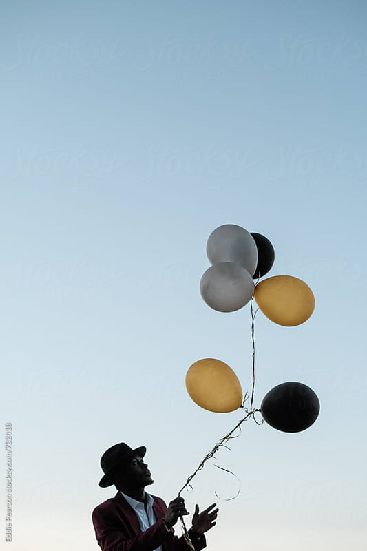 Dapper man tossing  balloons by Eddie Pearson for Stocksy United