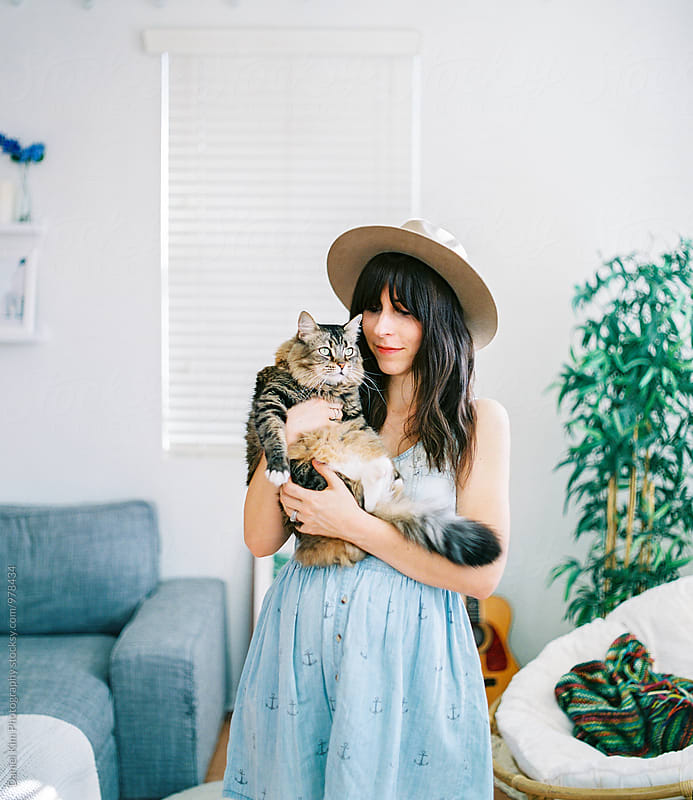 Young woman holding pet cat by Daniel Kim Photography for Stocksy United