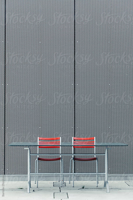 Metal chairs with red back and glass table  by Borislav Zhuykov for Stocksy United