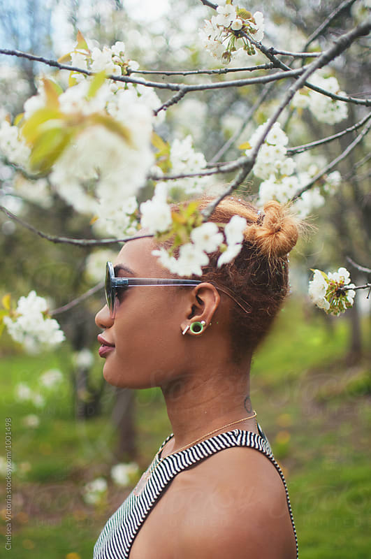 A young woman standing by a blossoming tree by Chelsea Victoria for Stocksy United