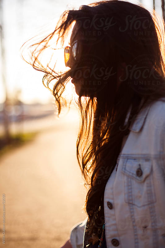 Backlit Portrait of Young Woman with Windblown Hair by Willie Dalton for Stocksy United