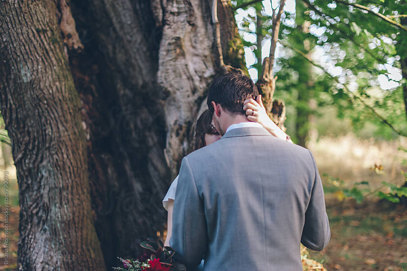 Couple Embracing in front of a Large Tree by Briana Morrison for Stocksy United
