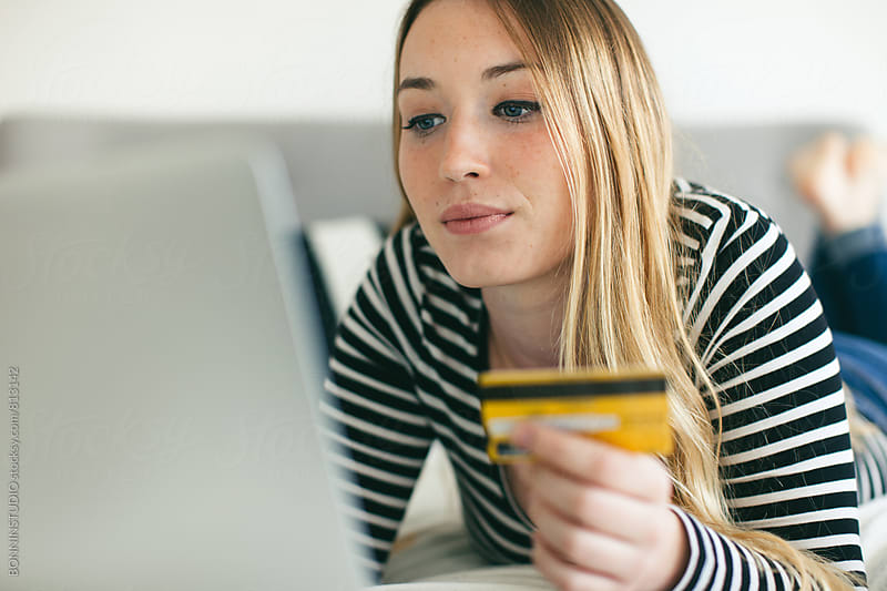 Woman shopping online with her credit card from home. by BONNINSTUDIO for Stocksy United