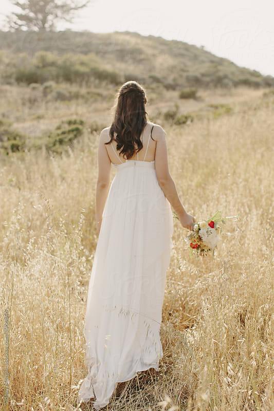 Bride Walking away in Field by Sidney Morgan for Stocksy United