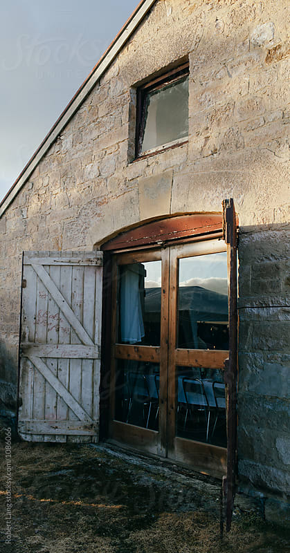 Barn style doors on an old stone building by Robert Lang for Stocksy United