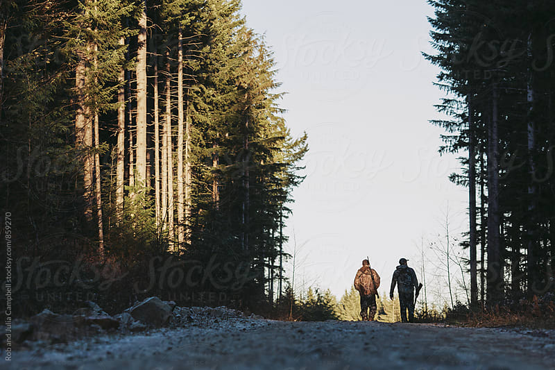 Two men hunting together outside in winter by Rob and Julia Campbell for Stocksy United