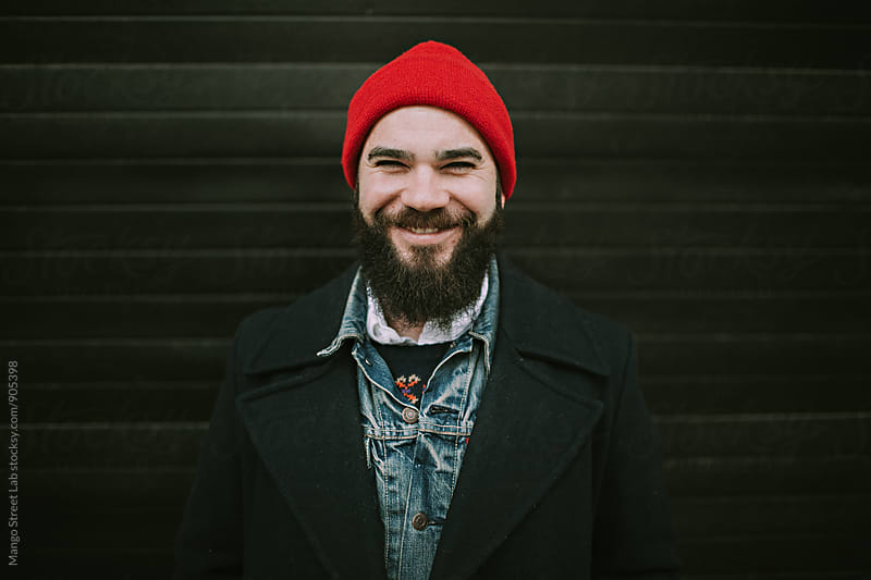 A Man Wearing a Red Beanie and Smiling  by Rachel Gulotta Photography for Stocksy United