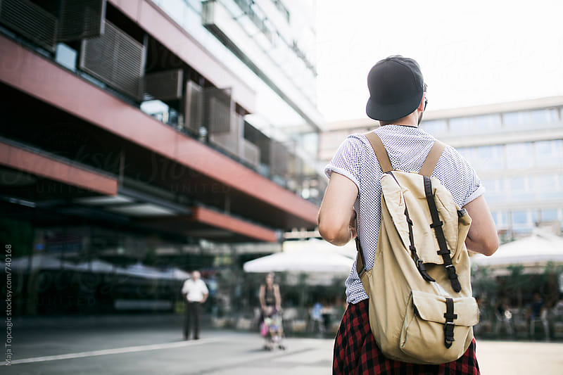 A man from the back with a rucksack by Maja Topcagic for Stocksy United