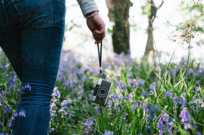 Woman walking through a bluebell wood with a camera in her hand by Suzi Marshall for Stocksy United