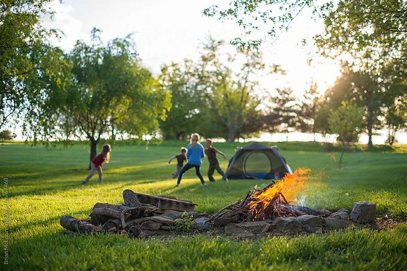 Backyard Camp Out: Children Play Tag with Campfire in Foreground by Brian McEntire for Stocksy United