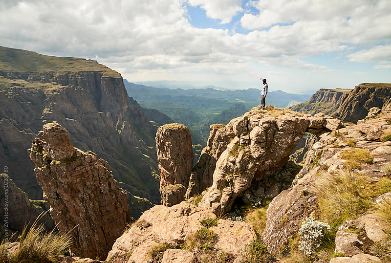 A Male hiker standing on rock stage with a natural bridge  above an epic mountainous valley. by Jacques van Zyl for Stocksy United