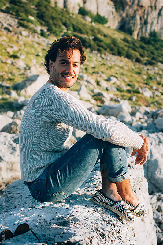 Outdoor Portrait of Good-Looking Young Italian Man Sitting on Boulder in Warm Sunset Light by Julien L. Balmer for Stocksy United