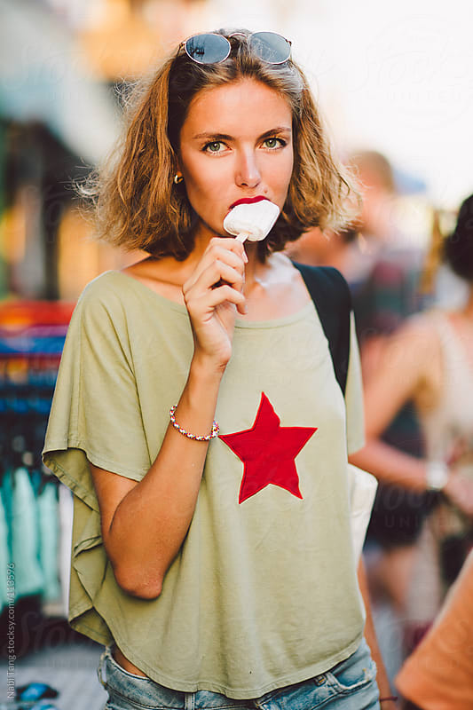 Beautiful young traveller eating ice cream on the street in Thailand by Nabi Tang for Stocksy United