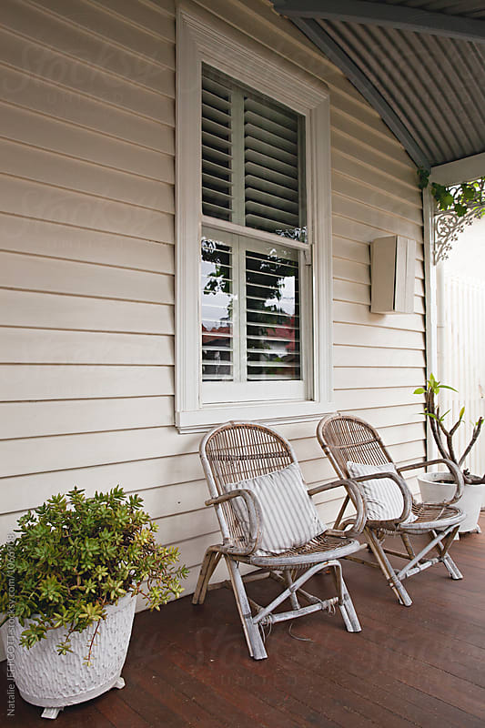 Two vintage cane chairs with cushions on front porch  by Natalie JEFFCOTT for Stocksy United