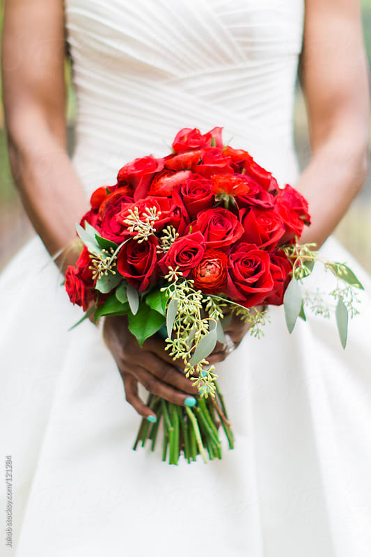 An african-american bride holding a bouquet of red roses. by Jakob for Stocksy United