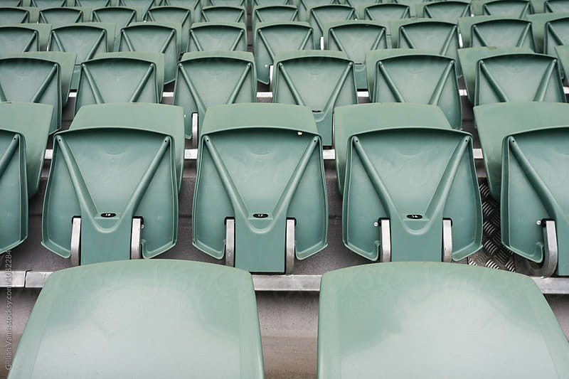 stadium seats, empty, except for that bit of gum on seat 17 by Gillian Vann for Stocksy United
