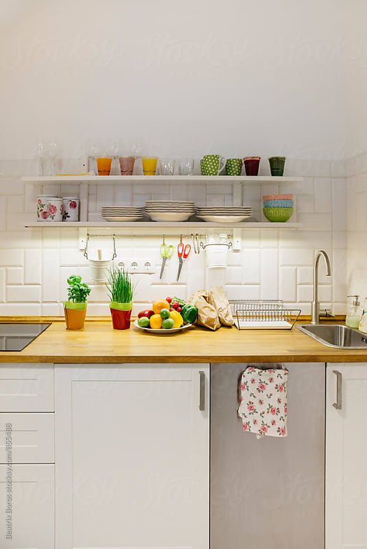 Vertical photo of a small kitchen with raw fruits and veggies on the counter by Beatrix Boros for Stocksy United