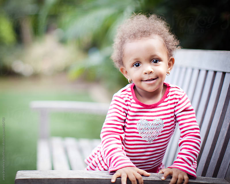 Portrait of toddler sitting on a bench smiling sweetly by anya brewley schultheiss for Stocksy United