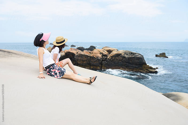 Side view of two tourists relaxing on rock against of sea by Lawren Lu for Stocksy United