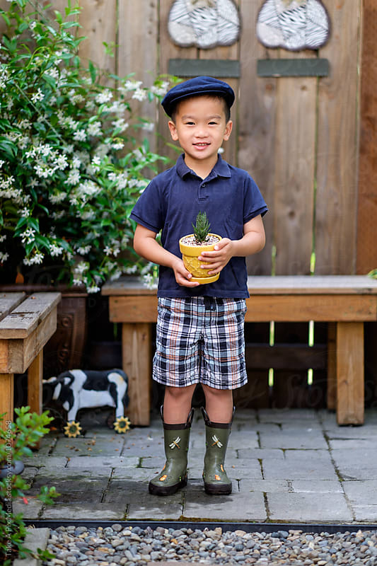 Asian kid holding a potted plant in the backyard by Suprijono Suharjoto for Stocksy United