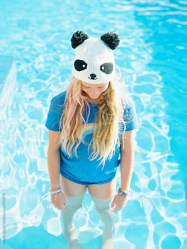 girl in rainbow tee wearing panda hat standing in swimming pool by wendy laurel for Stocksy United