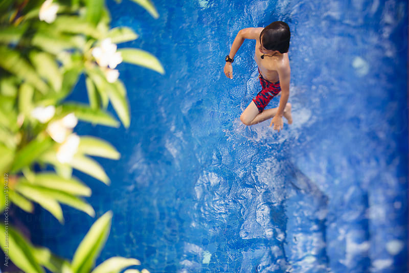 Boy in a blue swimming pool viewed from above by Angela Lumsden for Stocksy United