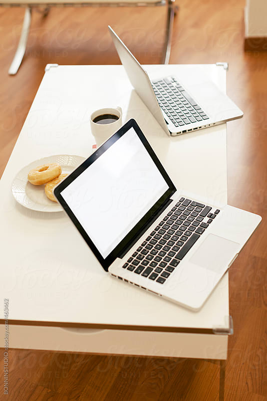 Still life of two laptops and breakfast on a table. by BONNINSTUDIO for Stocksy United