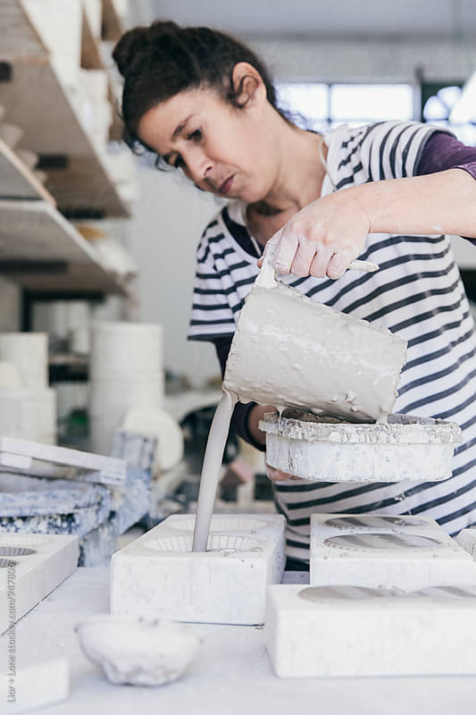 Female ceramic artist pouring wet slip into ceramic moulds by Lior + Lone for Stocksy United