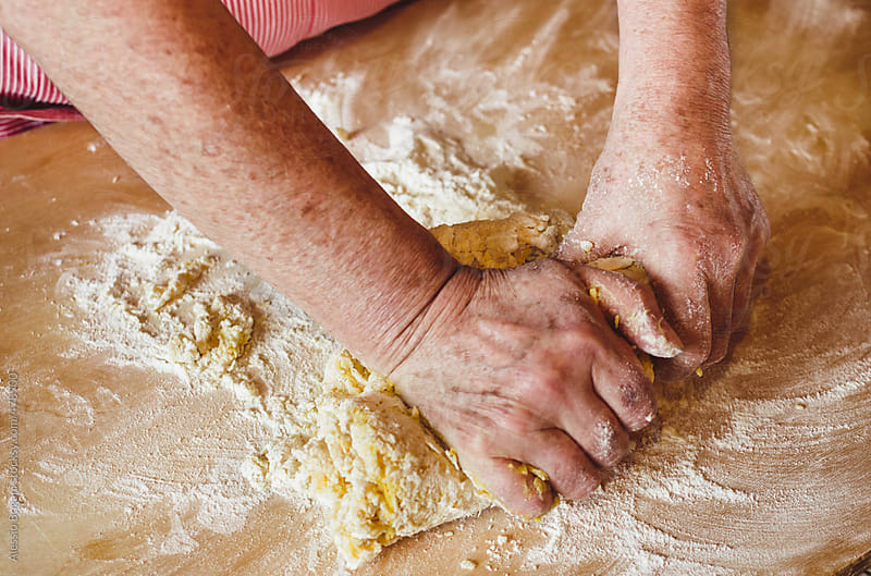 Italian woman kneading pasta dough by Alessio Bogani for Stocksy United