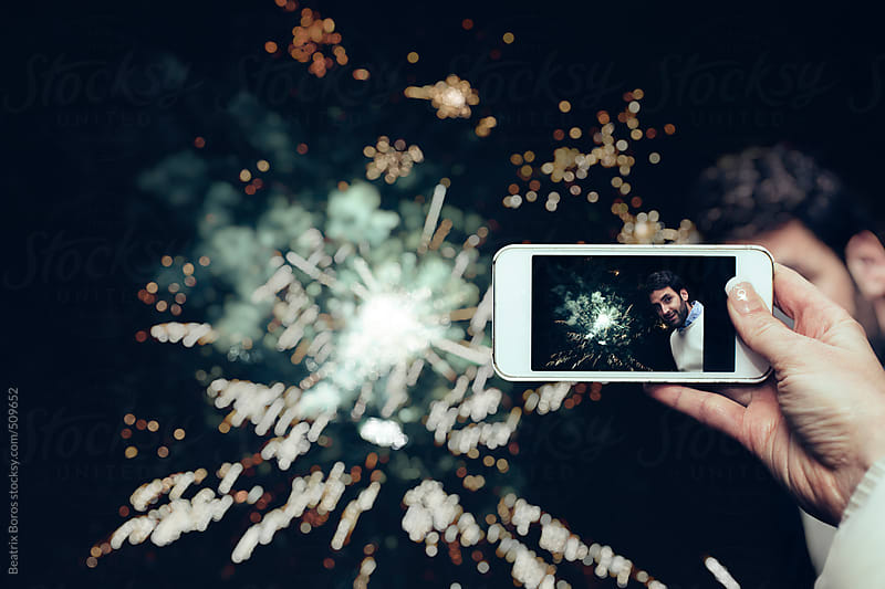 A female hand holding a mobile phone, and taking a photo of a man in front of fireworks by Beatrix Boros for Stocksy United