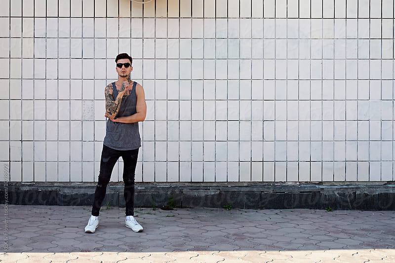 Young man with tattoos in sunglasses against of white ceramic wall by T-REX & Flower for Stocksy United
