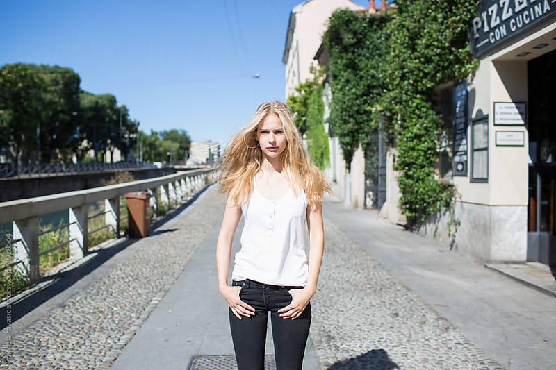 Beautiful blond girl standing alone in the street by michela ravasio for Stocksy United