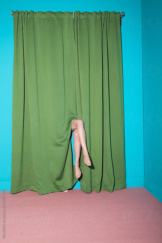 legs of a lady hiding behind the curtain in a room by Ulaş and Merve for Stocksy United