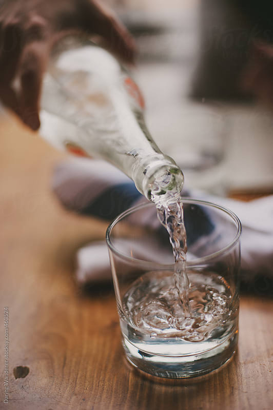 Woman pouring water from glass bottle into drinking glass at resturant by Daring Wanderer for Stocksy United