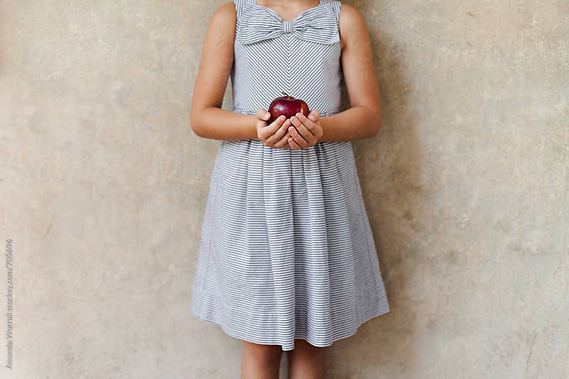Girl wearing striped dress with bow detail holding an apple against neutral wall by Amanda Worrall for Stocksy United