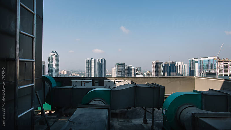 The city skyline viewed from the top of a building in a commercial business district by Lawrence del Mundo for Stocksy United