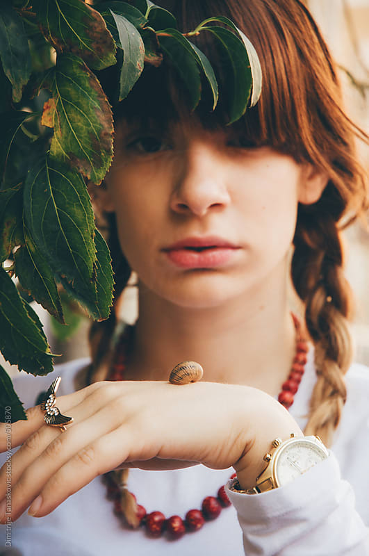 Beautiful young woman holding and watching snail on her hand by Dimitrije Tanaskovic for Stocksy United