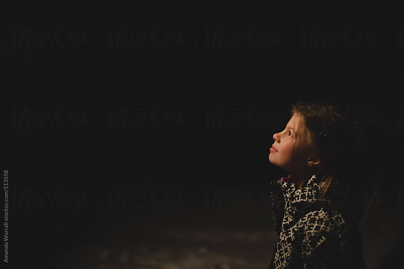 Profile of young girl looking up at night sky in winter by Amanda Worrall for Stocksy United