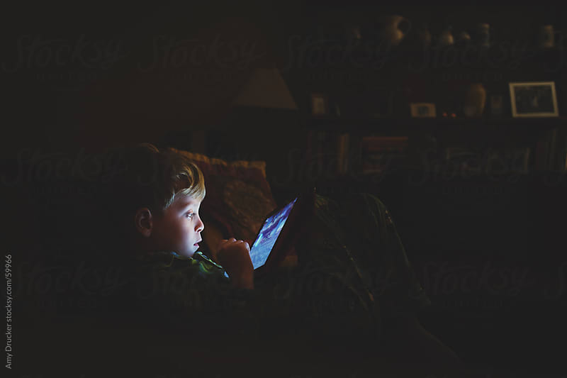 Young Boy Watching iPad by Amy Drucker for Stocksy United