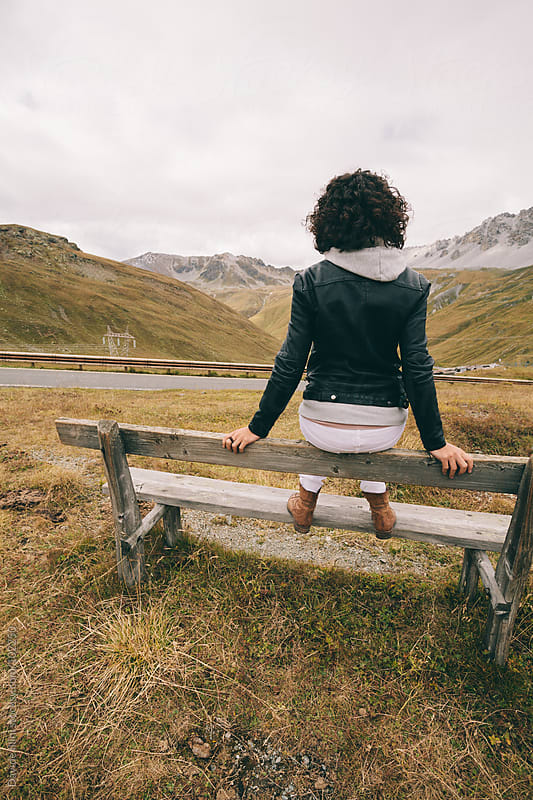 Young woman on a bench in the Stelvio National Park by Davide Illini for Stocksy United