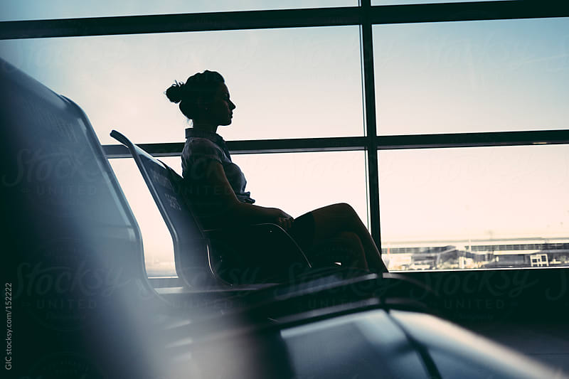 Young woman sitting in airport lounge by GIC for Stocksy United