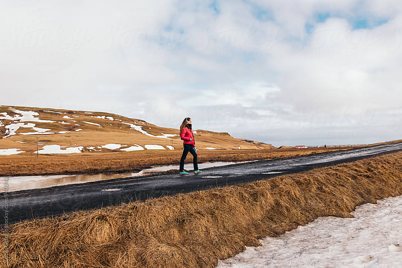 On the distance: woman in the middle of a rural road by Lucas Ottone for Stocksy United