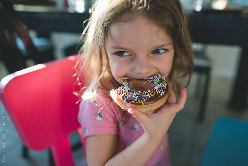 little girl eating a donut by Courtney Rust for Stocksy United