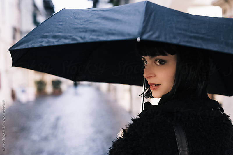 Woman walking outdoor during a rainy day by Mauro Grigollo for Stocksy United
