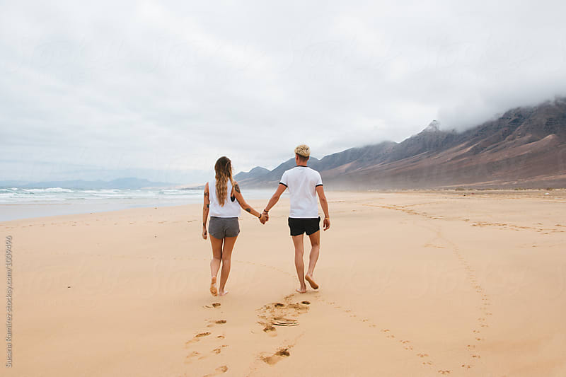 Young couple walking along the beach by Susana Ramírez for Stocksy United