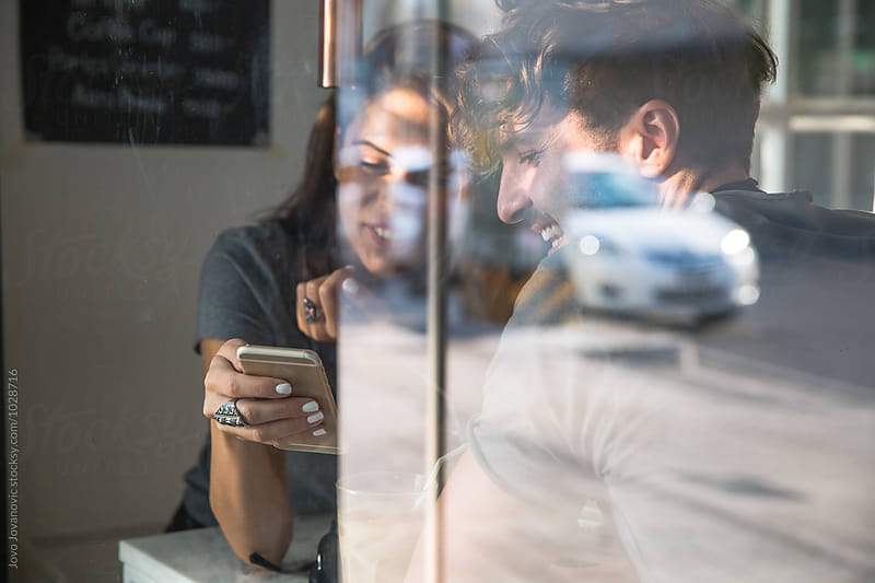 Couple on a date - looking at the phone by Jovo Jovanovic for Stocksy United