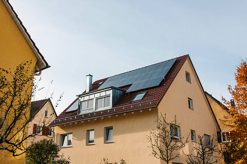 Solar panels on the roof of a yellow home in Germany. by Holly Clark for Stocksy United