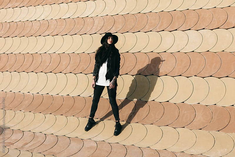 Alternative woman standing in front of a wall on winter. by BONNINSTUDIO for Stocksy United