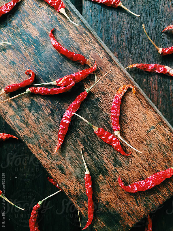 Red hot chillies scattered on a wooden background. by Shikhar Bhattarai for Stocksy United