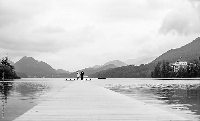 bridal couple walking on a jetty in beautiful lake landscape - black and white by Leander Nardin for Stocksy United